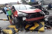 Toyota Sienta Tabrak Separator Busway hingga Terguling, Pengemudi Hendak Angkat Ponsel