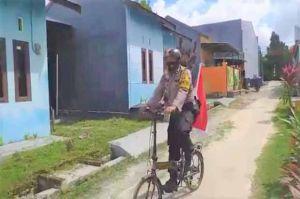 Bhabinkabtibmas Ini Keliling Pakai Sepeda Ingatkan Warga Pasang Bendera