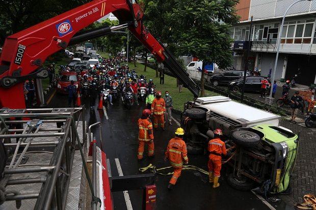 Selip Akibat Ban Terlalu Halus, Truk Pengangkut Buah Terguling Melintang di Tengah Jalan